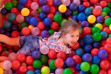 Fototapeta na wymiar Baby girl is playing in playground with colourful balls