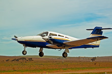 Low Flying Blue And White Twin Engine Aircraft