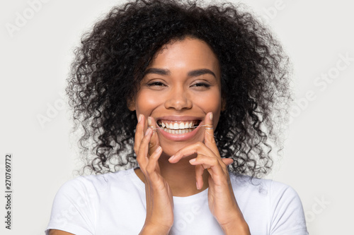 Stampa su Tela  Closeup portrait happy african woman cleaning teeth with dental floss