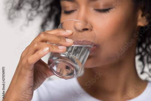 Fotografia, Obraz Close up african millennial female holding glass drinking water