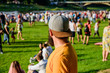 canvas print picture - Hipster in cap happy celebrate event fest or festival. Summer fest. Man bearded hipster in front of crowd. Open air concert. Fan zone. Music festival. Entertainment concept. Visit summer festival