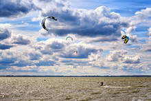 Many Men In The Water Between The Waves. Kitesurfing Kiteboarding Action On The Sea.
