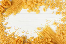 A Set Of Different Types Of Italian Pasta On A Colored Background Top View, Place For Text.