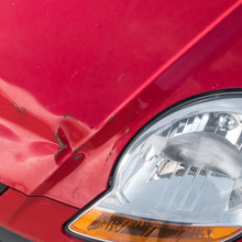 Scratches And Rusty Dent On Front Of Red Car