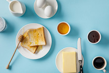 Top View Of Served Breakfast With Yogurt, Milk, Coffee, Jam, Honey, Butter And Knife, Toasts On White Plates On Blue Background