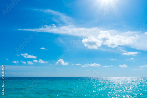Foto auf Leinwand Blau Jeans White clouds with blue sky and sun over calm sea in tropical Maldives island .