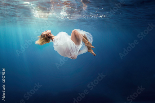 Fotografia Blonde girl wrapped in fine white cloth, sank in blue deep water of ocean, against dark sea background