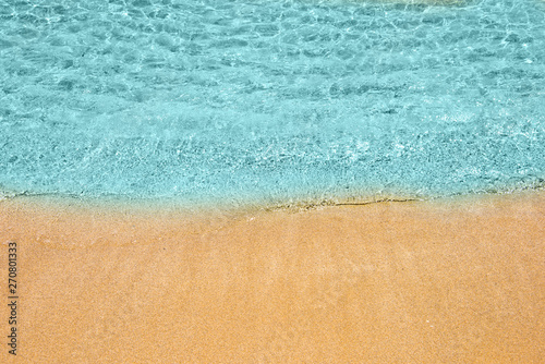 Soft wave of turquoise sea water on the sandy beach