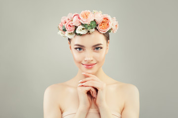 FototapetaBeautiful smiling woman spa model with clear skin and tender rose flowers. Skincare and facial treatment concept