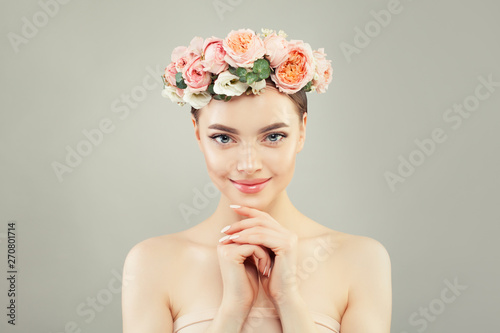 Beautiful smiling woman spa model with clear skin and tender rose flowers. Skincare and facial treatment concept