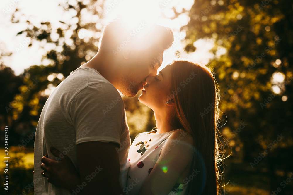 Fototapety, obrazy: Side view portrait of a amazing couple kissing against sunset outside while traveling in their vacation time.