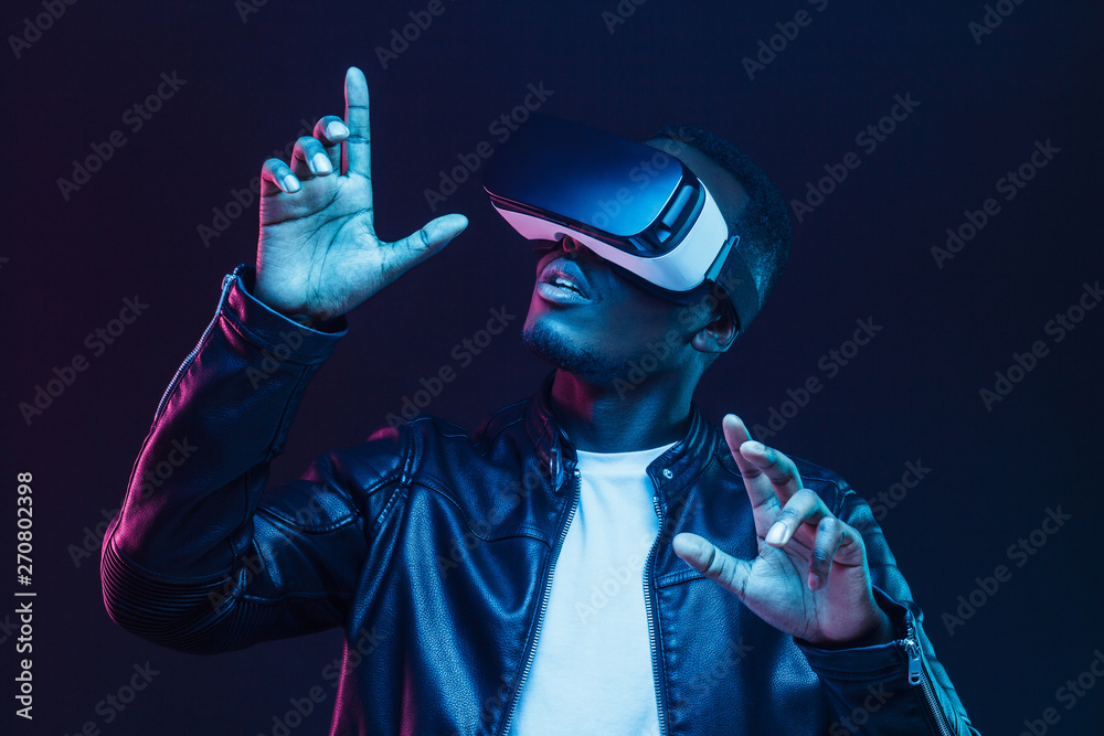 Fototapeta Portrait of African guy isolated on black background wearing headset of virtual reality