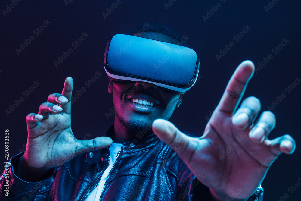 Fototapeta African man wearing virtual reality headset having great fun