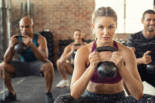 Poster Fitness Fitness woman squatting with kettle bell
