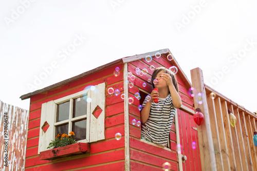 Fototapeta Boy blowing bubbles in a wooden playhouse