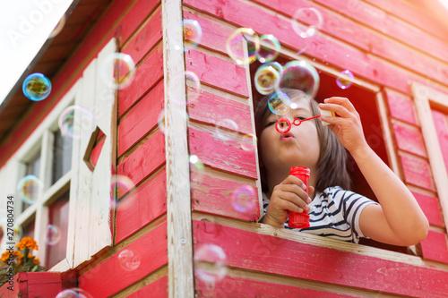 Obraz na plátne Boy blowing bubbles in a wooden playhouse