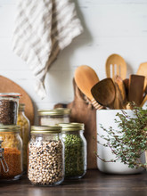 Various Cereals And Seeds - Peas, Beans, Rice, Pasta, Flax, Lentils In Glass Jars On The Table In The Kitchen