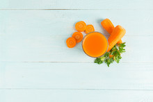 A Glass Of Fresh Carrot Juice On A Wooden Blue Background. Copy Space. Flat Layout Top View