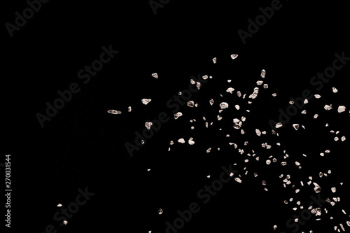 Foto op Canvas Kruiderij Split debris of stone exploding against black background.