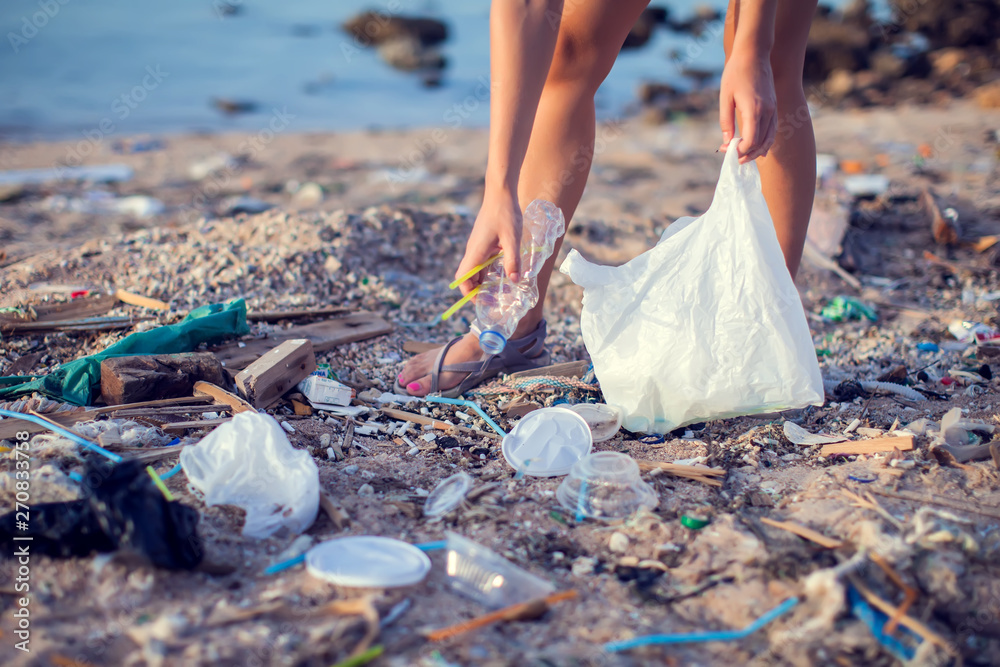 Fototapety, obrazy: Woman collect garbage on the beach. Environmental pollution concept