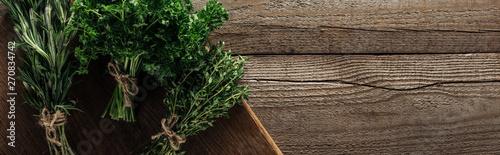 panoramiczny-strzal-zielony-rozmaryn-pietruszka-i-tymianek-na-desce-do-krojenia-na-drewnianym-stole-wyblakly-z-miejsca-kopiowania