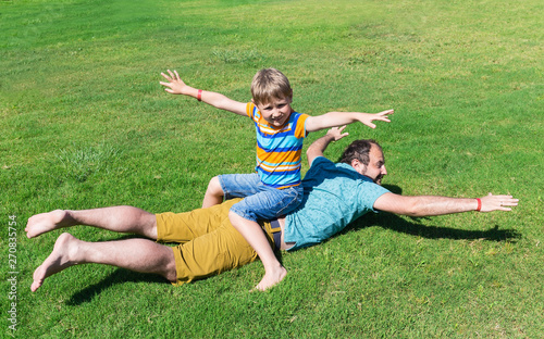 Photo Dad and son rest on grass on sunny summer day