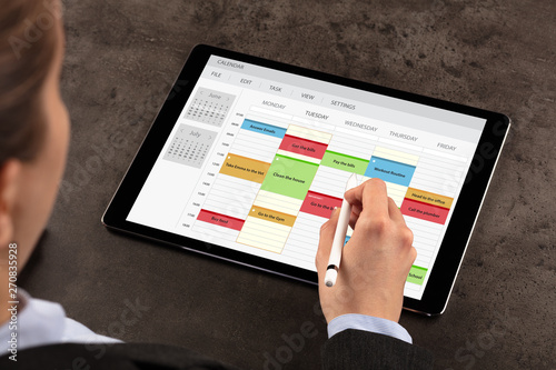 Obraz Business woman schedule her weekly program on tablet  - fototapety do salonu