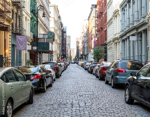fototapeta na ścianę Cobblestone covered Greene Street is crowded with buildings and cars in the SoHo neighborhood of Manhattan in New York City