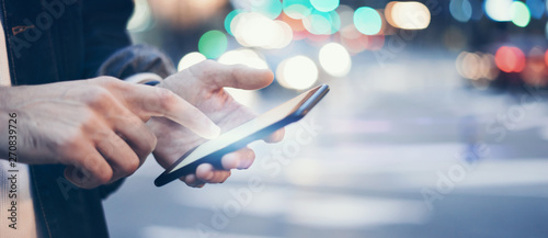 Fotografering  Closeup image of male hands with smartphone at night on city street, searching i