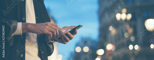 Obraz Closeup image of male hands with smartphone at night on city street, searching internet or social networks, hipster man typing an sms message on chat - fototapety do salonu