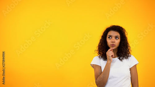 Thoughtful black woman touching chin and looking up, choosing between options Wallpaper Mural