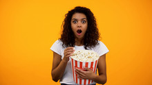 Excited African-American Woman Eating Popcorn And Watching Interesting Movie