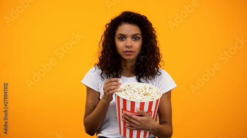 Fotografie, Obraz  Beautiful African-American woman eating popcorn isolated on yellow background