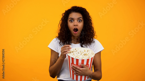 Photo  Excited African-American woman eating popcorn and watching interesting movie