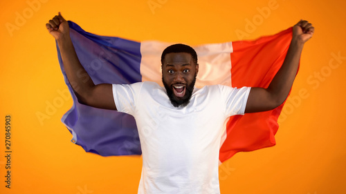 Excited black man holding French flag, supporting national sports team, cheering Canvas Print