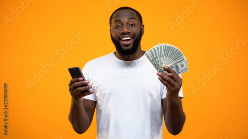 Excited Afro-American man holding smartphone and dollars, online money transfer Tableau sur Toile
