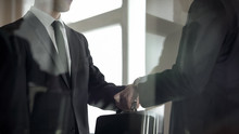 Man Handing Over Briefcase To Another Man In Business Suit, Secret Transfer
