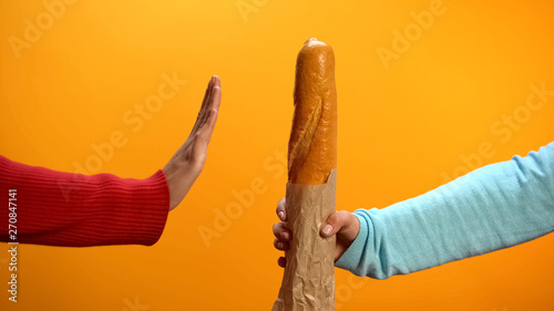 Valokuvatapetti Hand showing stop sign rejecting fresh baked baguette on bright background