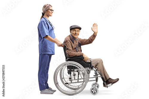 Female nurse pushing a senior patient sitting in a wheelchair and greeting with Canvas Print