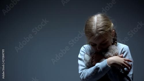 Fotografie, Obraz  Lonely little child hugging teddy bear, bullying concept, dark background