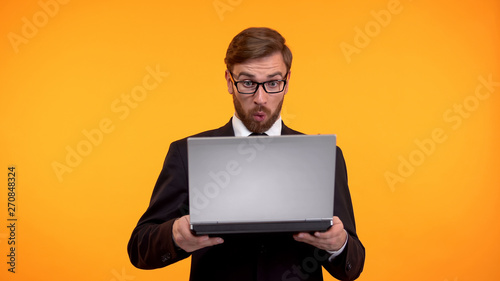 Photo Shocked man looking with astonishment at computer, high interest rate, taxes