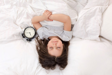 cute little child girl in pyjamas with clock in bed. good morning. top view