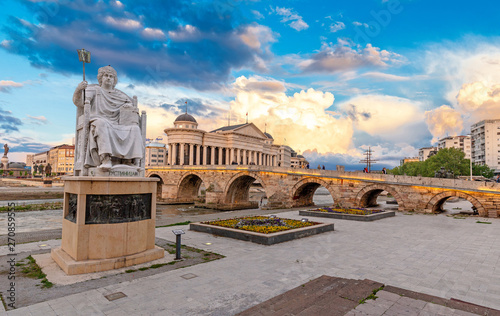 Staande foto Oude gebouw SKOPJE, NORTH MACEDONIA - 25.04.2019: Byzantine Emperor Justinian Statue and Stone Bridge, behind the Archeology Museum at sunset in Skopje