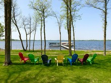 Colorful Lawn Chairs On Green Grass Near Lake Shore With Boat And Pontoons On Lifts At Dock On A Sunny Day