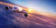 Leinwandbild Motiv Commercial airplane jetliner flying above dramatic clouds in beautiful sunset light. Travel concept.