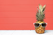 Hipster pineapple with sunglasses against a living coral colored wood background. Minimal summer concept.