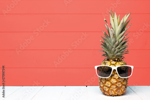 Photo  Hipster pineapple with sunglasses against a living coral colored wood background