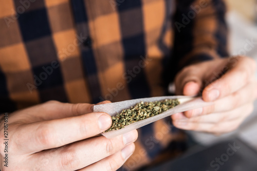 Fotografija  Man preparing and rolling marijuana cannabis joint