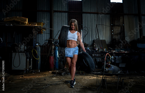 sexy girl in overalls with working tools in a big hangar