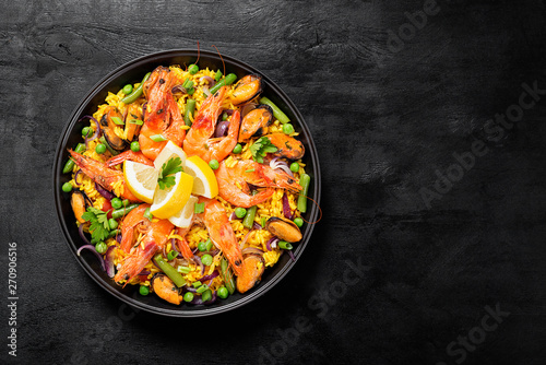 Traditional spanish seafood paella in the fry pan on a black wooden  table, top view Fototapet